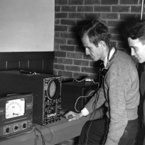 Engineering research staff members with electric oscillator