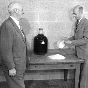 Dr. E. M. Schoenborn and Dean J. H. Lampe comparing stickwater