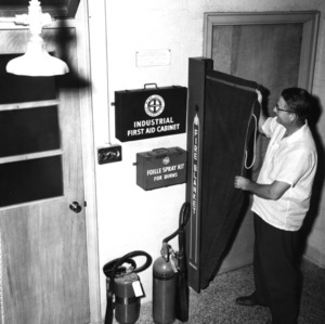 """Dr. F.P. Pike showing safety and first aid equipment installed in lab used for study of """"Liquid-Liquid Extraction"""""""