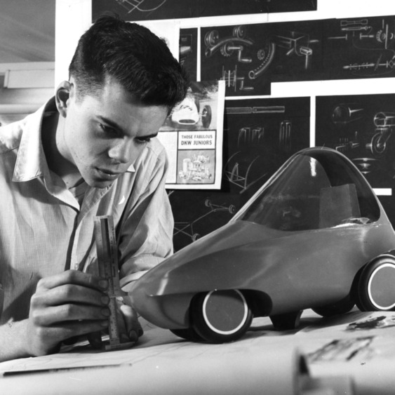 Engineering student measuring model of car, circa 1950s