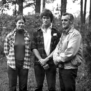 Dean Eric Ellwood in woods with two forestry students