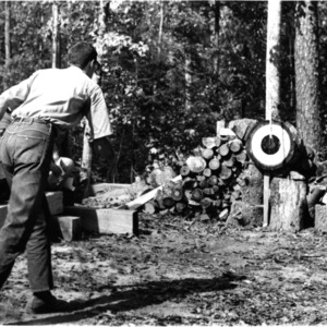 Student throwing ax at bullseye, 1950s?
