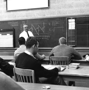 Prof. Goerge E. Tucker, in charge of the Furniture Manufacturing and Management curriculum at North Carolina State, lectures on furniture manufacturing controls at the plant level in one of the furniture classes, 195-.