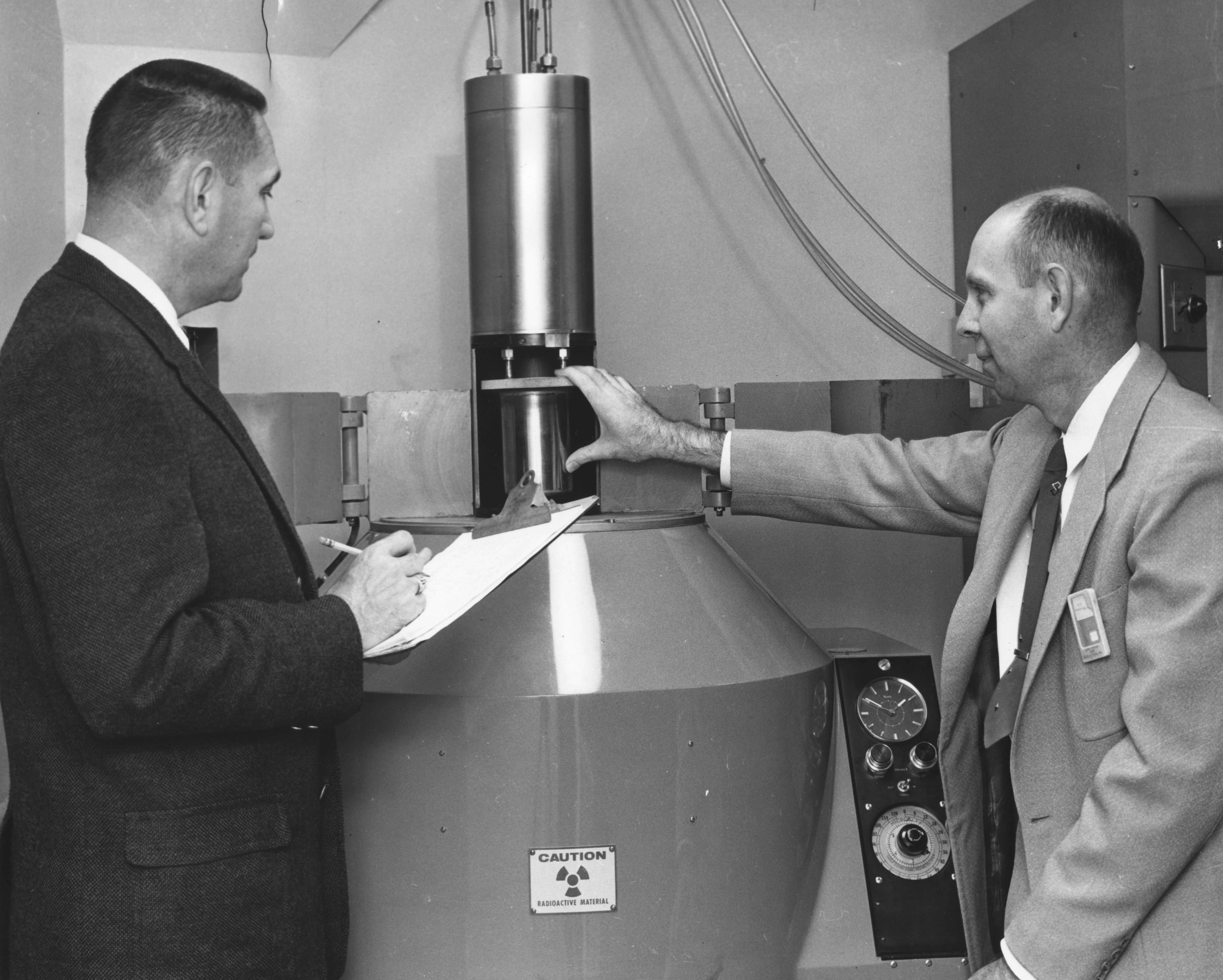Professor Henry A. Rutherford (left) and Dr. A. Armstrong examine the Cobalt-60 source in the college's radiological laboratory