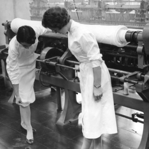 Two researchers with a tricot warp knitter in a laboratory at the School of Textiles, North Carolina State College.