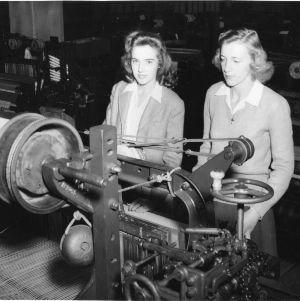 Two students with textile machinery, North Carolina State College School of Textiles.
