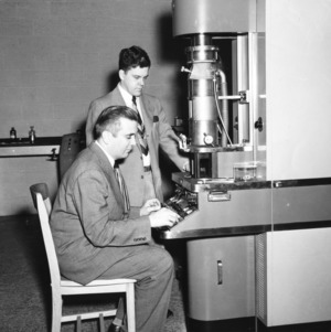 Dr. Arthur C. Menius and Dr. Kenneth O. Beatty with electron microscope