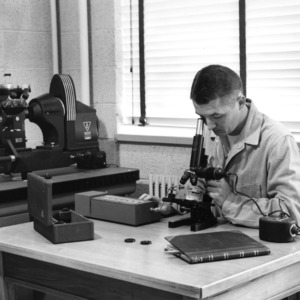 Dr. Benjamin F. Brown researching with Hurlbut counter attached to a metallurgical microscope