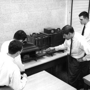 Professor Sigurd Johnson explaining operation of De Burgh furniture finishing conveyor to students in Furniture Plant Layout Laboratory