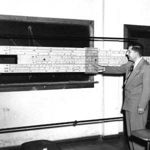 Dr. John W. Cell teaching at chalkboard with giant slide-rule