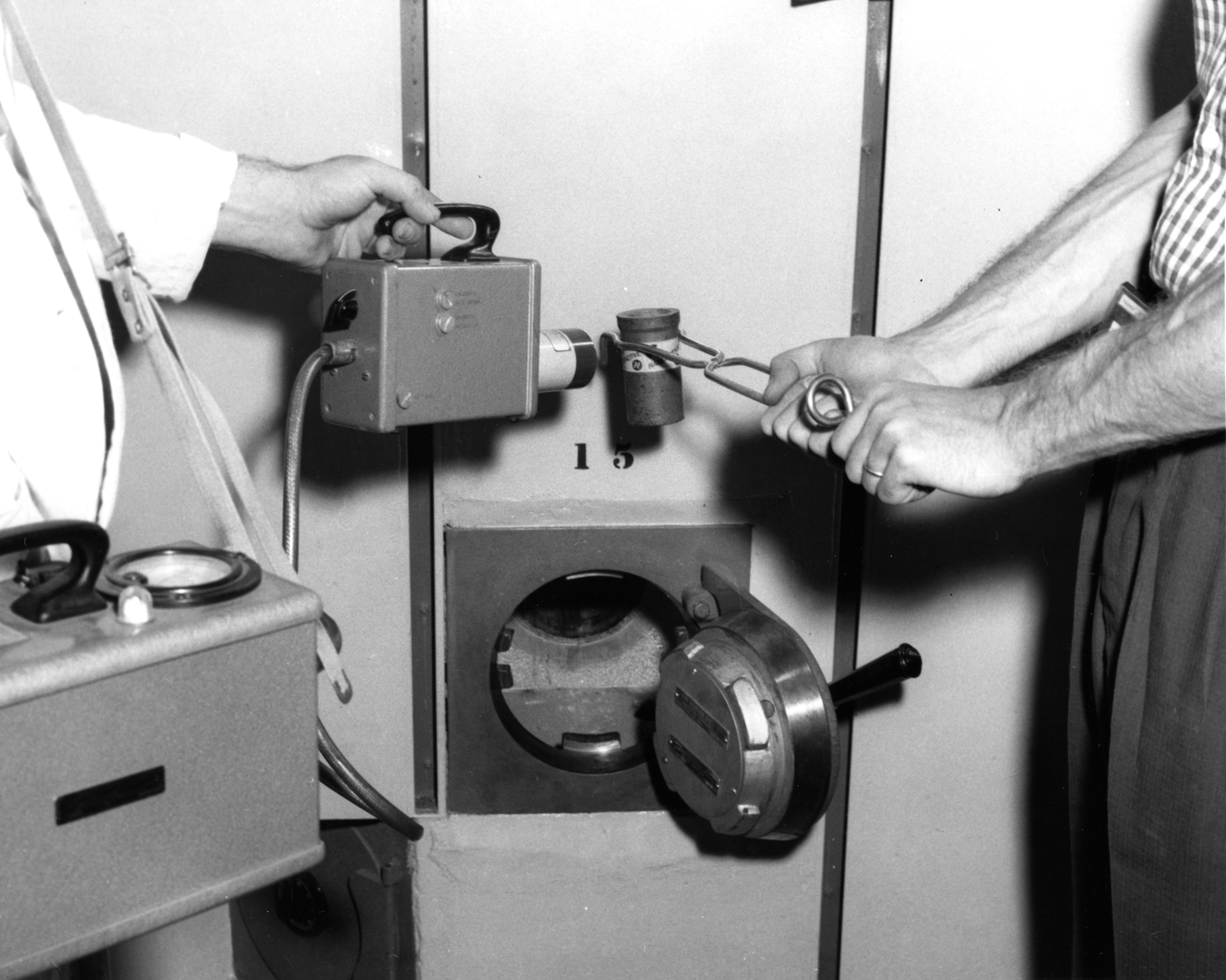 Researcher testing radioactivity level of sample with a geiger counter, 1950s?
