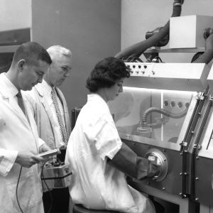 Researchers working with radioactive materials in laboratory, 1950s?