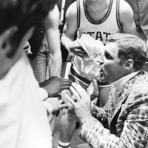 Monte Towe and Coach Sloan in time-out huddle, N.C. State University basketball