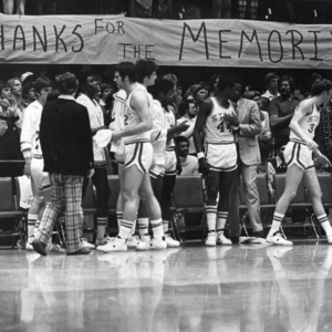 "N.C. State University basketball sidelines during UNC Charlotte game with banner that reads ""Thanks for the memories"""
