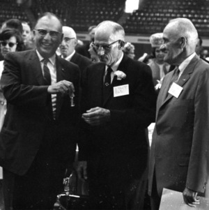 H. W. (Pop) Taylor (center) receiving keys to a Pontiac car during his retirement dinner, May 8, 1965.