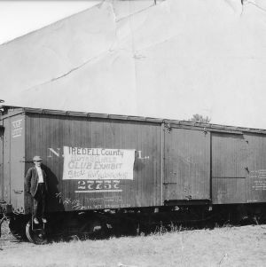 "County agent standing on the steps of a train car with sign reading ""Iredell County Boys and Girls Club Exhibit State Fair Raleigh, October 15-20"""