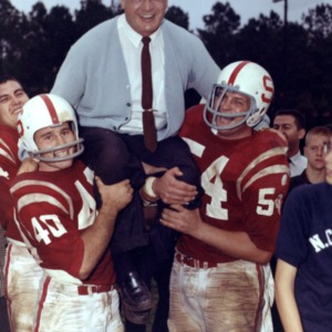 Earle Edwards carried by his players after winning a game