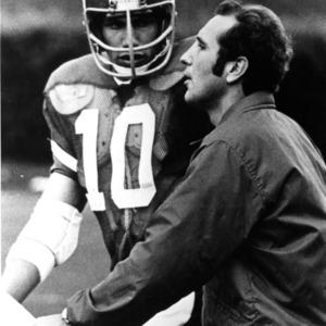 N. C. State coach Bo Rein talking to quarterback Johnny Evans on field