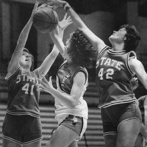 Newspaper photograph of N.C. State's Connie Rogers and Karen Thompson on defense against Carolina opponent