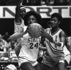 N.C. State's #24 Karen Brabson about to pass under heavy guard from two Carolina players