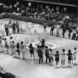 Basketball team and fans dancing in gym