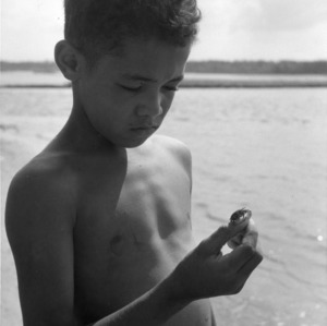 4-H club member holding a hermit crab while attending the 4-H Wildlife Conference, Aug 5-10, 1957
