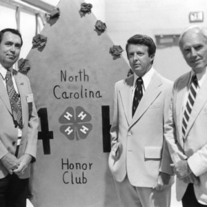 Chester Black and others standing with the North Carolina 4-H Honor Club emblem