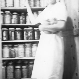 4-H club girl showing off her canned goods as part of a 4-H home economics program
