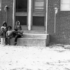 Five young African-American children sitting on a door step