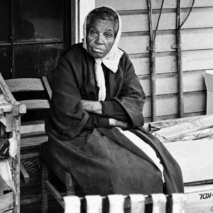 Elderly African American woman sitting on her porch