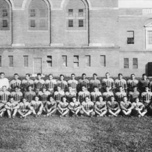 North Carolina State College football team posing behind Thompson Gymnasium.