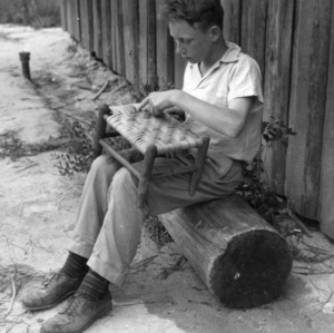 4-H club member weaving cane onto stool at Camp Millstone