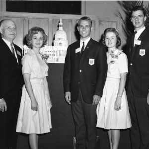 North Carolina delegates and L. R. Harrill standing in front of a model of the Capital building while attending the National 4-H Camp in Washington, D.C.