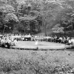 4-H members gathered around fire circle at Camp Millstone