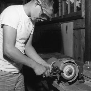 4-H club member grinding blade in model farm shop at Millstone 4-H Camp