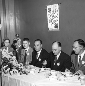 4-H club members and leaders, including L. R. Harrill, attending a dinner