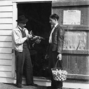 4-H club boy holding a basket of eggs while a man inspects a chicken outside poultry house
