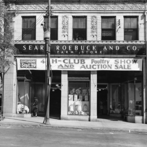 Exterior of Sears, Roebuck and Company Farm Store with banner advertising 4-H club poultry show and auction sale