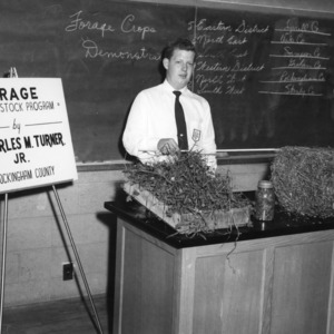 """Charles M. Turner, Jr., of Rockinham County, North Carolina, with an exhibit on """"Forage in a Livestock Program,"""" during North Carolina State 4-H demonstration competition, 1957"""