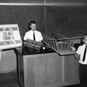 """Billy Boyette and Nelson Waters of Sampson County with an exhibit on """"Making and Feeding Silage from a Horizontal Silo"""" during North Carolina State 4-H demonstration competition"""