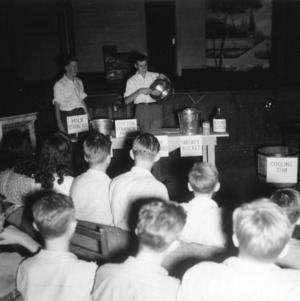 Two 4-H club boys giving a dairy demonstration to a group of 4-H club members