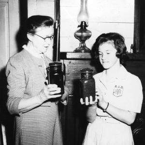 4-H club girl and leader examining jars used for canning as part of a 4-H food preservation program