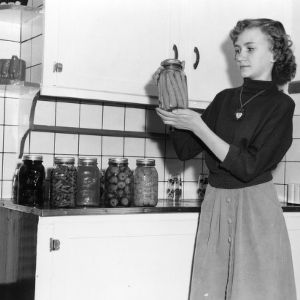 4-H club girl posing in kitchen with jars of preserved foods
