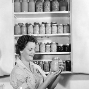 4-H club girl examining canned foods as part of a 4-H food preservation program