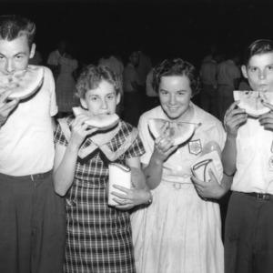 Four 4-H club members eating watermelon during North Carolina State 4-H Club Week, July 1958