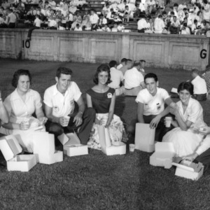4-H club members picnicking with box lunches on football field during North Carolina State 4-H Club Week, July 1958