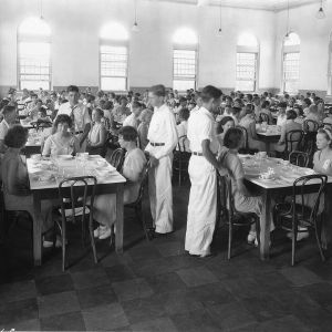 Boys pulling out chairs for girls in dining hall at North Carolina State 4-H Short Course, 1932