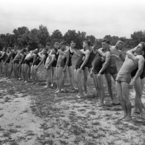 Instructor teaching young men water lifesaving techniques, at North Carolina State 4-H Short Course, 1932