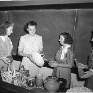 4-H club members examining pottery and basketry while attending North Carolina State 4-H Short Course at North Carolina State College, July 1941