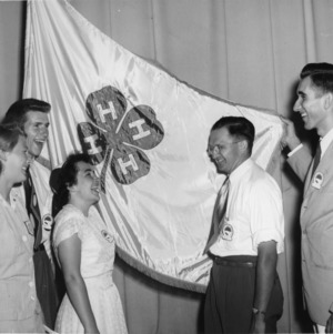 4-H club members standing in front of the 4-H flag while attending North Carolina State 4-H Club Week